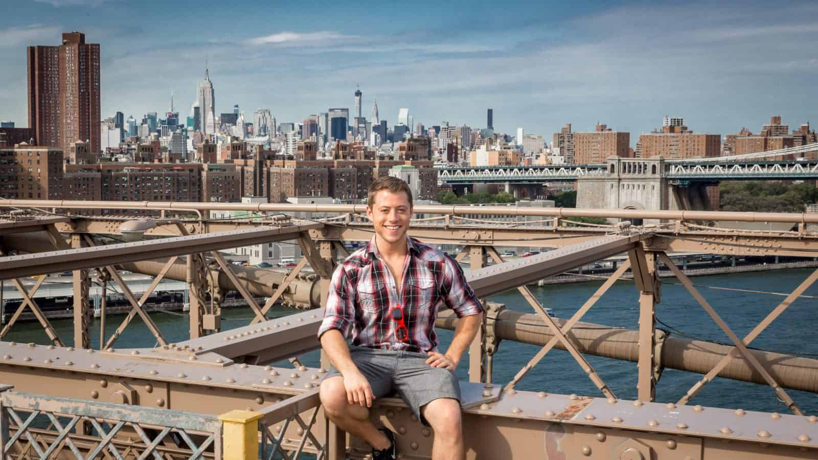 Jeremy Foster sitting on the Brooklyn Bridge in New York City