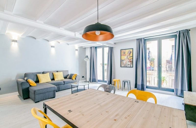 a modern apartment with grey couches and yellow chairs