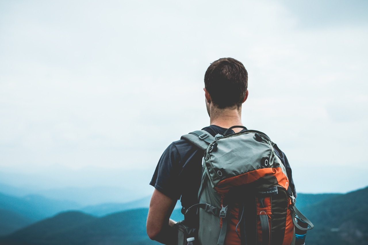 a man with a backpack looks out over the mountains