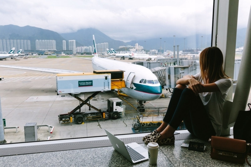 Girl at airport, looking at a plane on the tarmac