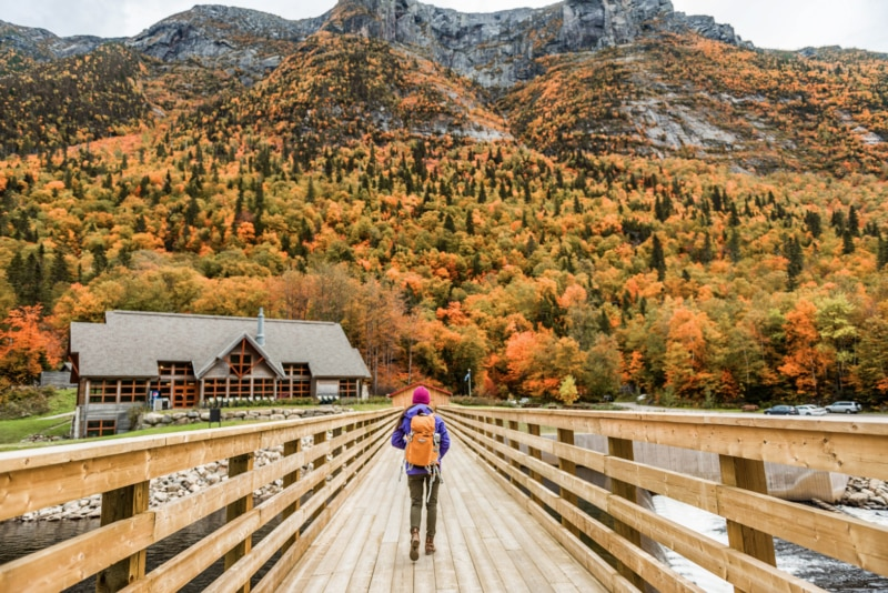 A woman walking in Quebec surrounded by fall colors in nature.