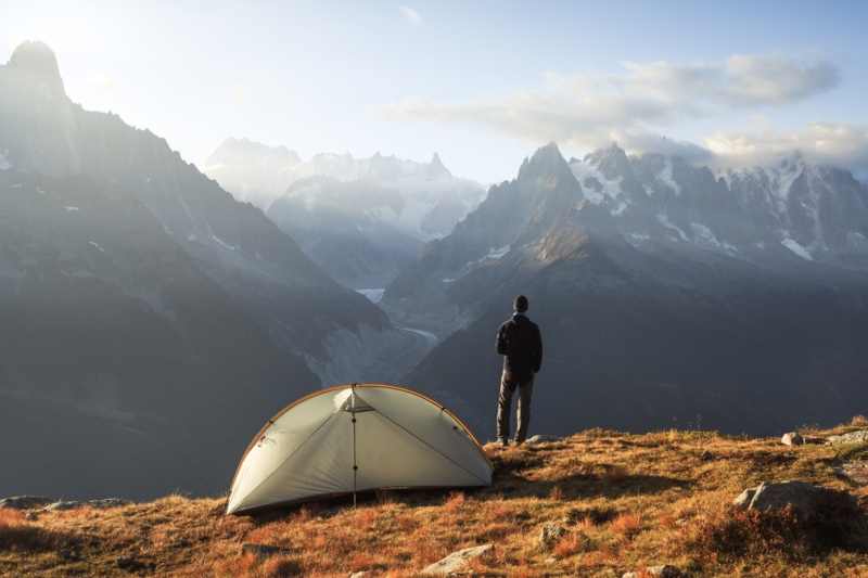Hiker enjoying the view and a cup of coffee at his campsite in the mountains