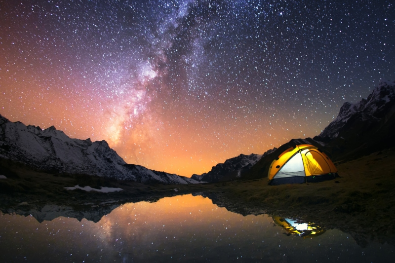 View of stars and backpacking tent at night at a lake.