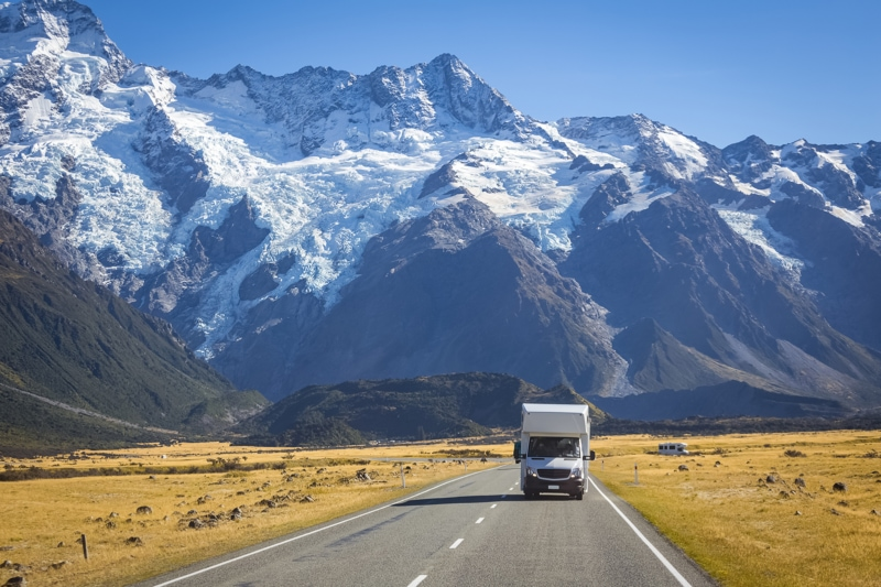 a rented RV driving through the snow capped mountains
