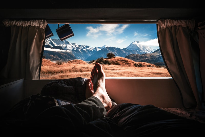 A man sticks his feet out of a rented RV in the mountains