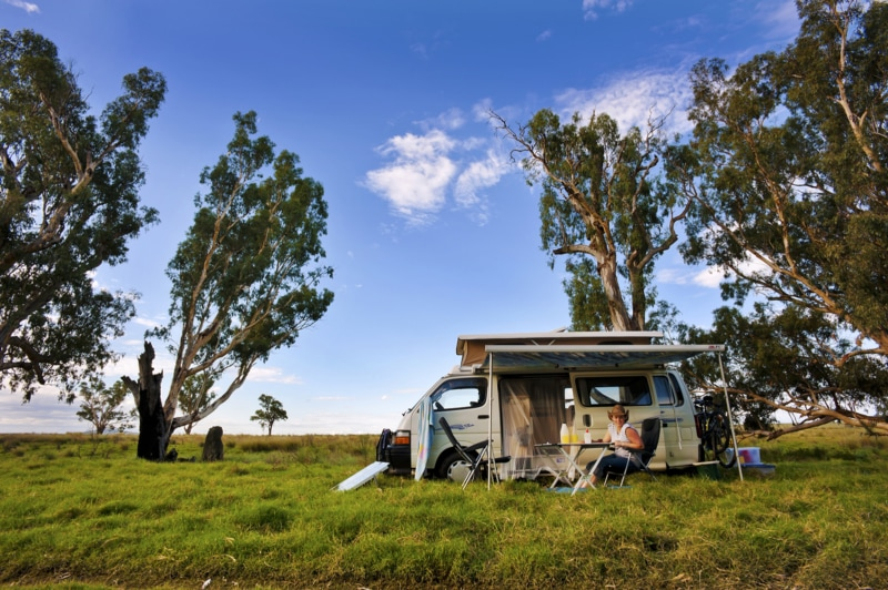 A woman sits at a table in front of her RV rental in a field