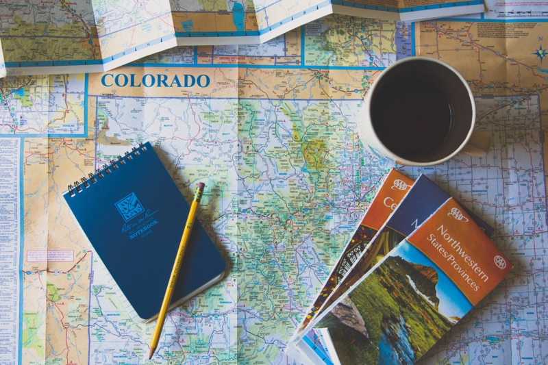 a map with a cup of coffee and travel planning tools