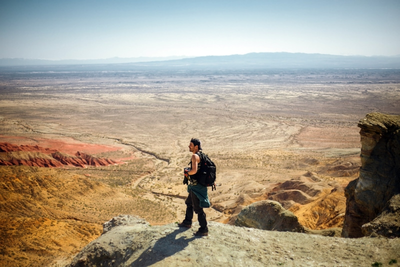 photographer with a backpack standing on a ledge overlooking a desert