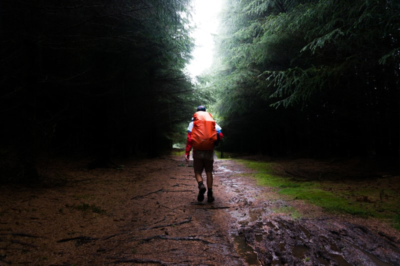 a man with an orange backpack walking through a muddy trail