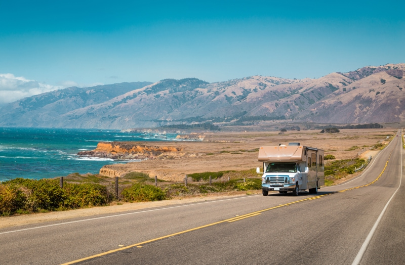 A large RV from one of the best RV rental companies drives along the California Highway 1