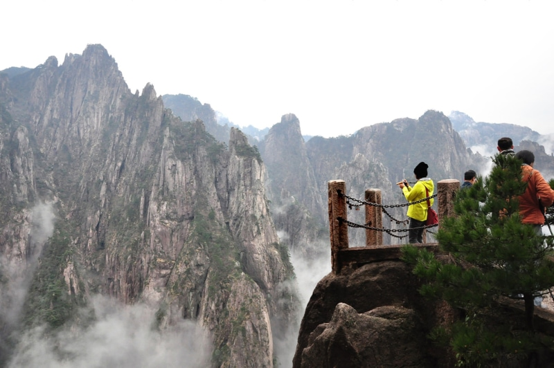 a woman stands at a lookout taking photos of a gorge in China