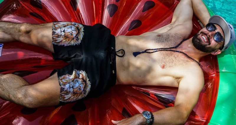 Model lounges on inflatable watermelon wearing Kenny Flowers swim trunks