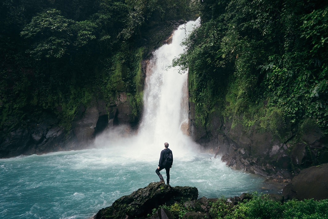 A man standing on a rock in front of a waterfall