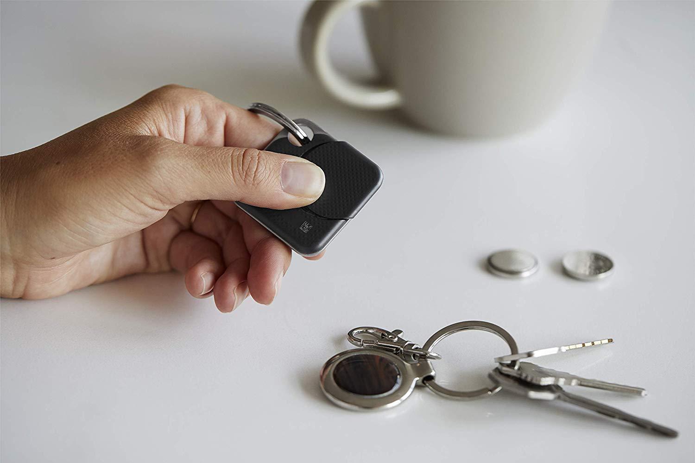 a hand holding a Tile Bluetooth Tracker next to a set of keys