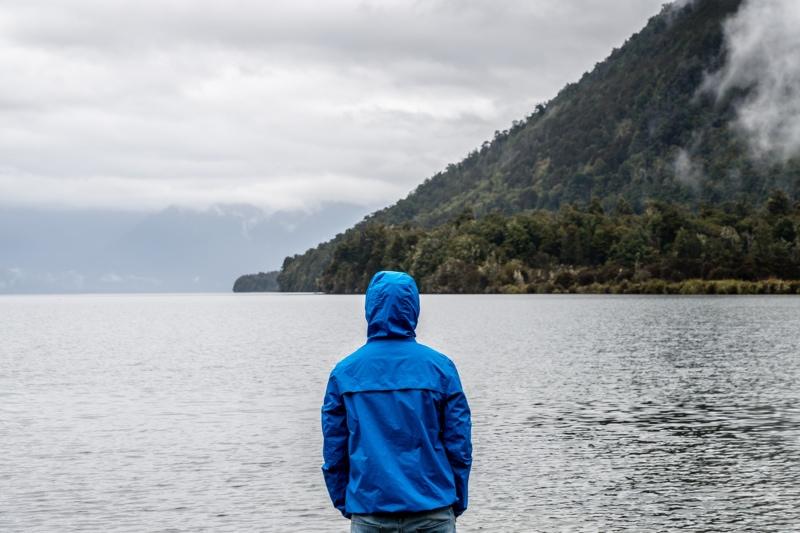 A man wearing a blue rain jacket faces a rainy ocean landscape
