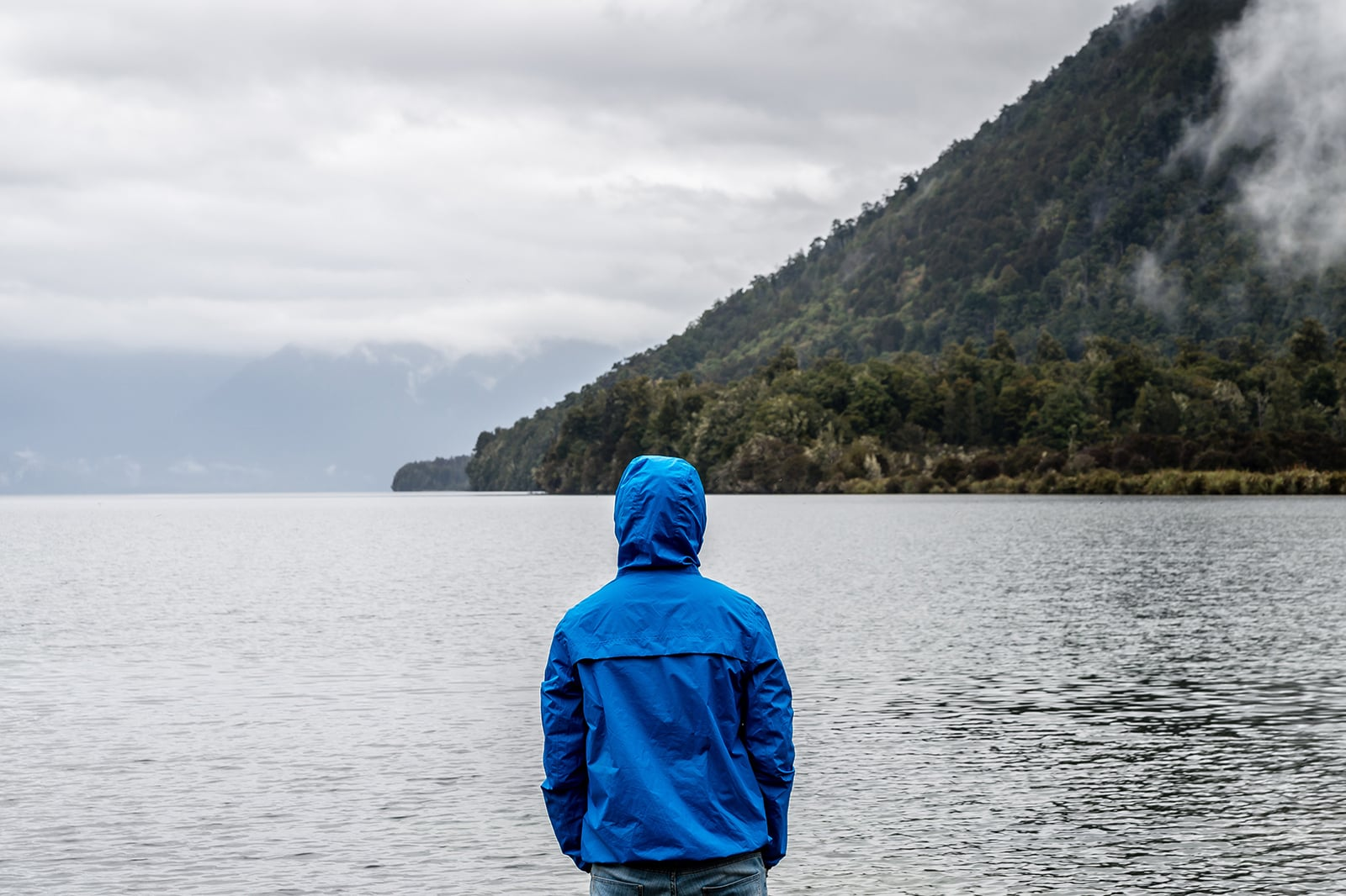 A man wearing a blue rain jacket faces a rainy ocean landscape