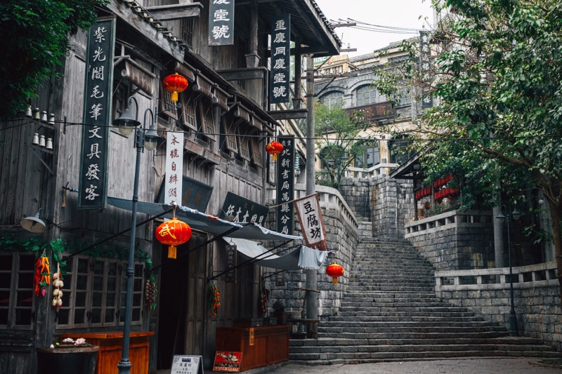 Orange lanterns and a tall staircase in a Chinese alleyway