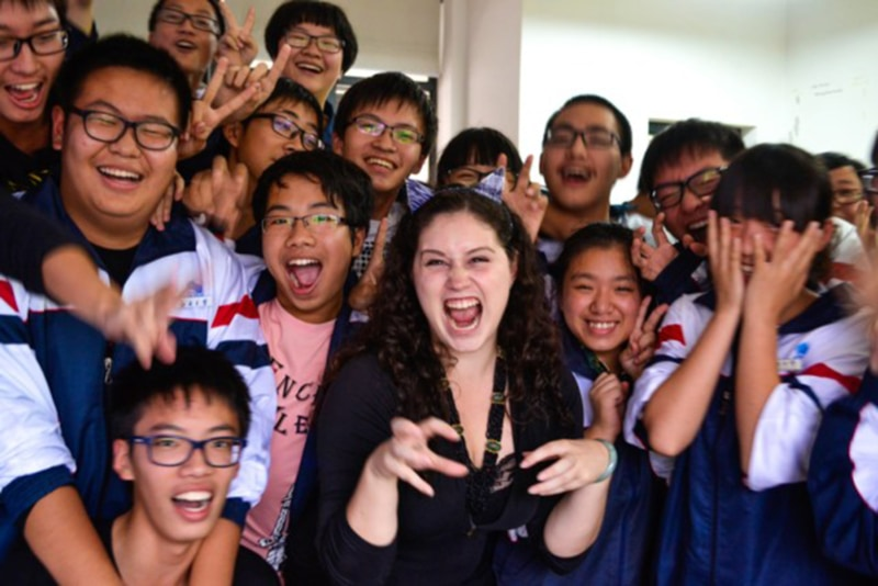 Richelle Gamlam posing with students in China