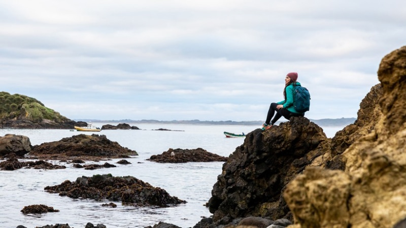 a woman sits on a coastal trail with an Osprey pack