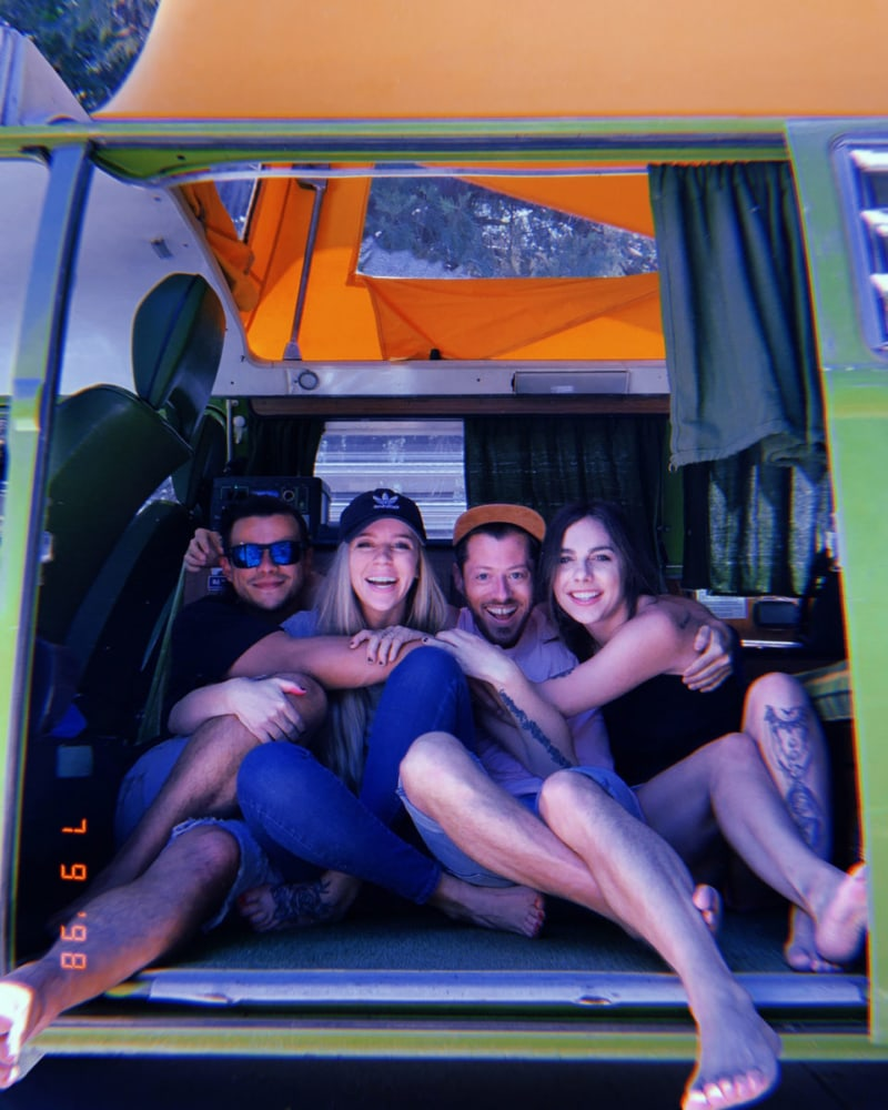 Four friends hanging out the back of a campervan rental