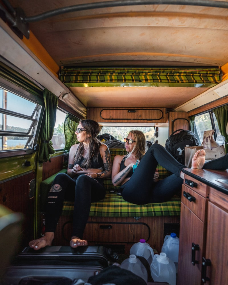 Two girls lounging in the back of a campervan