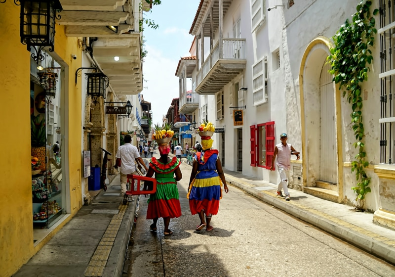 Two women in colorful clothing walk down a street in Cartagena, one of the best places to visit in Colombia