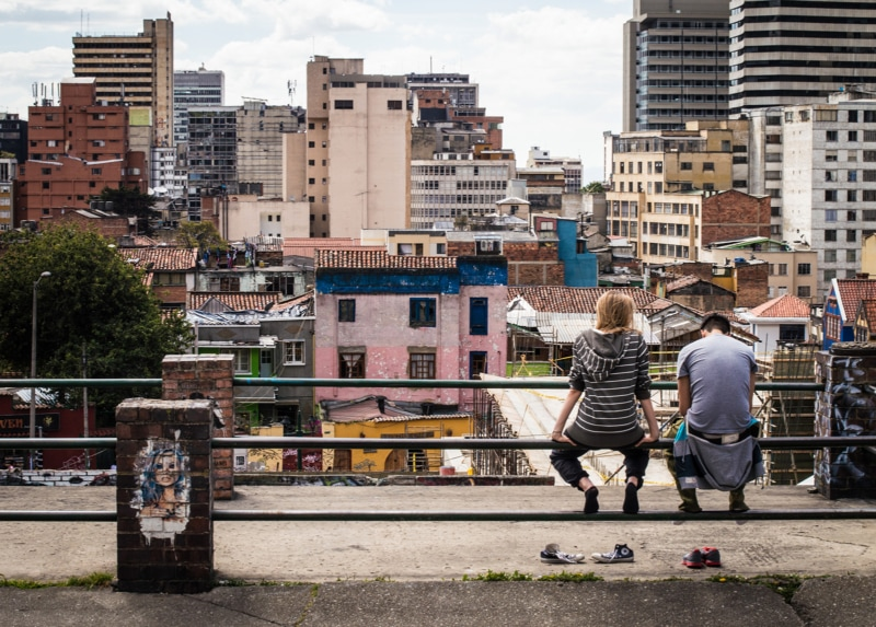 a couple sit on a bench overlooking the city of Bogota