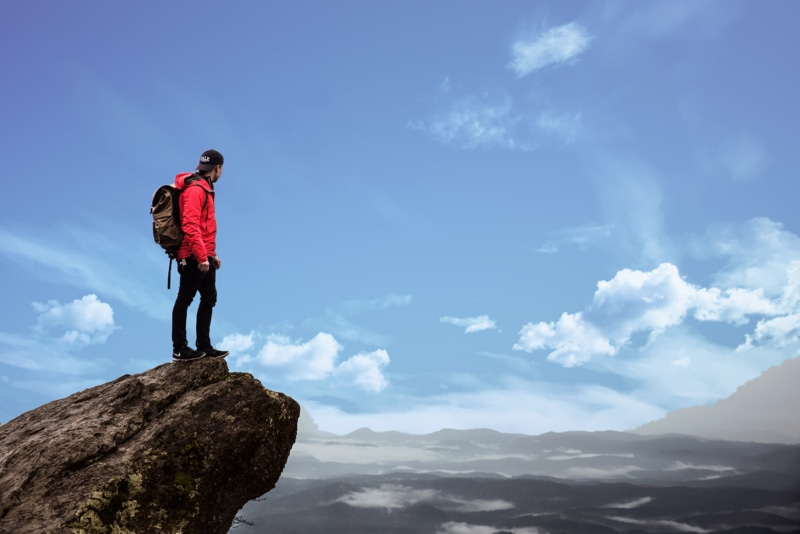 A hiker in a red jacket stands on a cliff with a backpack