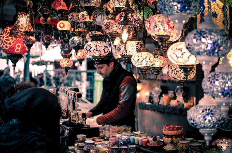 A man wearing a hat sorts through jewelry at a bazaar in Morocco