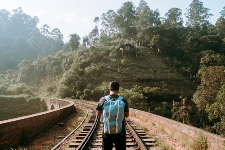 A man walks along train tracks wearing a blue backpack