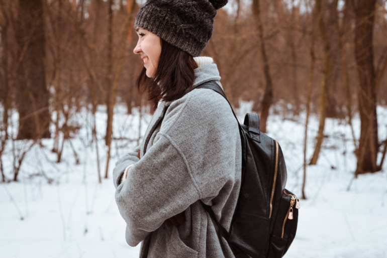 Portrait of a smiling girl with brown hair in  winter forest wearing a leather backpack
