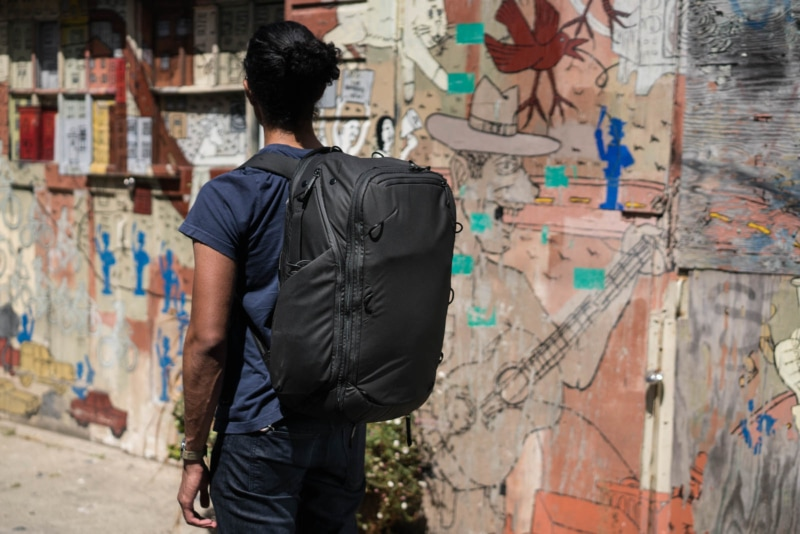 a man wearing a Peak Design Travel Backpack in front of a graffiti wall
