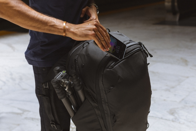 Peak Design Travel Backpack's organization pockets with a person putting a cellphone into the front pocket