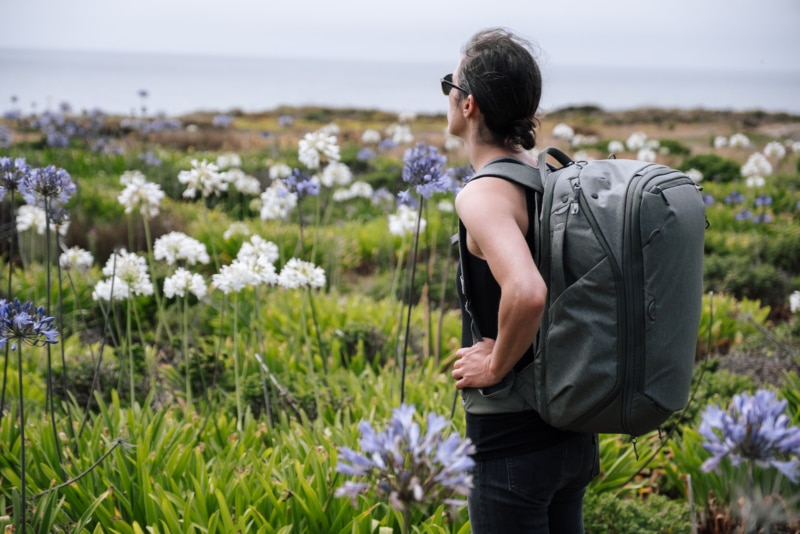 A woman standing in a field of flowers with her Peak Design Travel Backpack