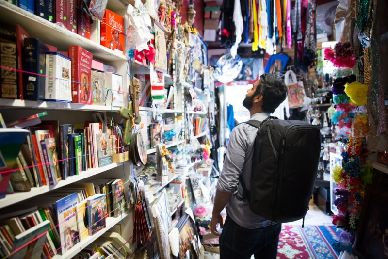 a man wearing a Peak Design Travel Backpack while perusing for souvenirs in a shop