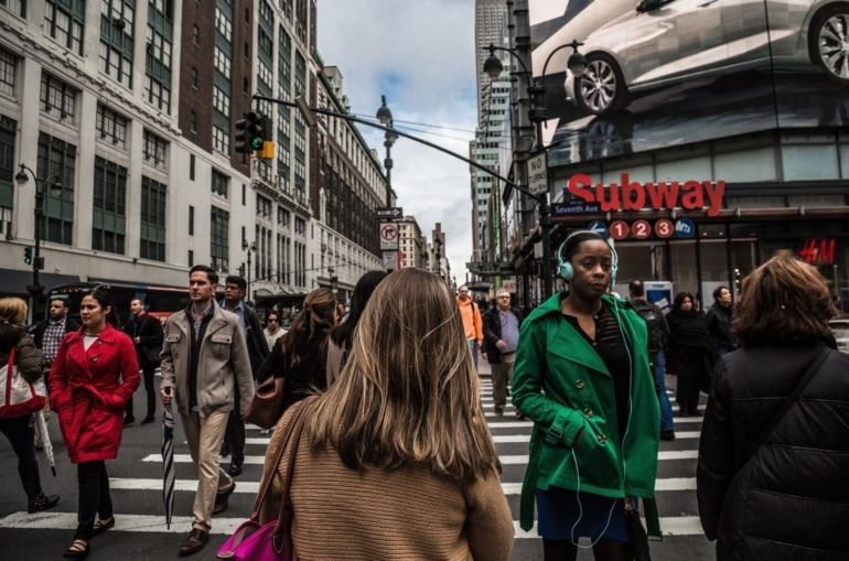 a young woman in a brown coat walks through a busy city intersection