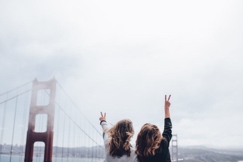 Two girls with peace signs in front of the Golden Gate Bridge in San Francisco