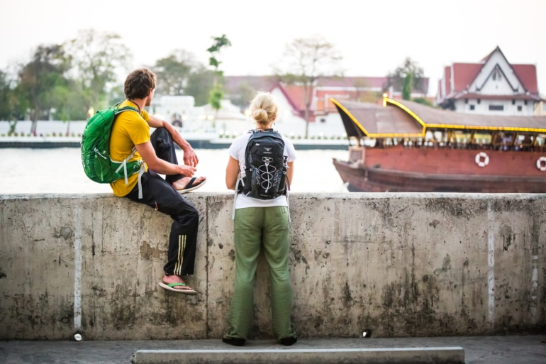 a man wearing an Osprey Talon 33 backpack and a woman wearing an Osprey Tempest backpack overlooking a river in Bangkok, Thailand
