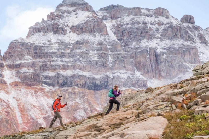 A man and a woman hiking up a mountain while wearing their 33 liters Osprey Talon and Tempest packs