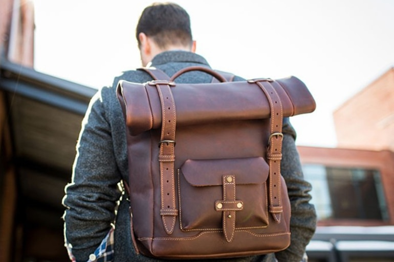 man wearing a brown Pad & Quill Heritage Rolltop leather backpack