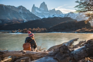 A woman with a leather backpack sits in front of Fitzroy Mountain in El Chalten, Argentina