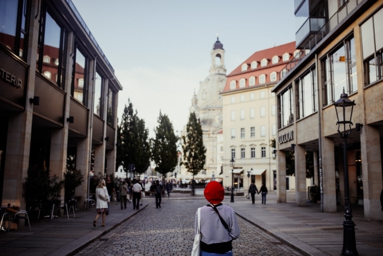 a woman wearing a red hat walking down the street in Dresden, Germany
