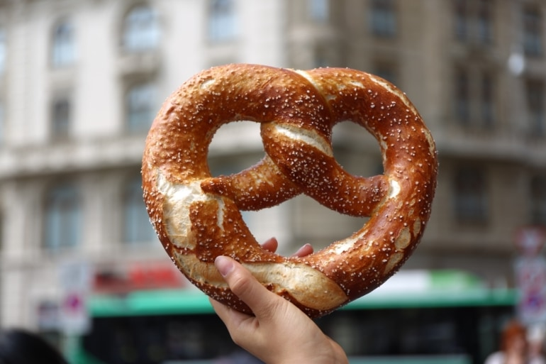 a woman holding a giant pretzel in Germany