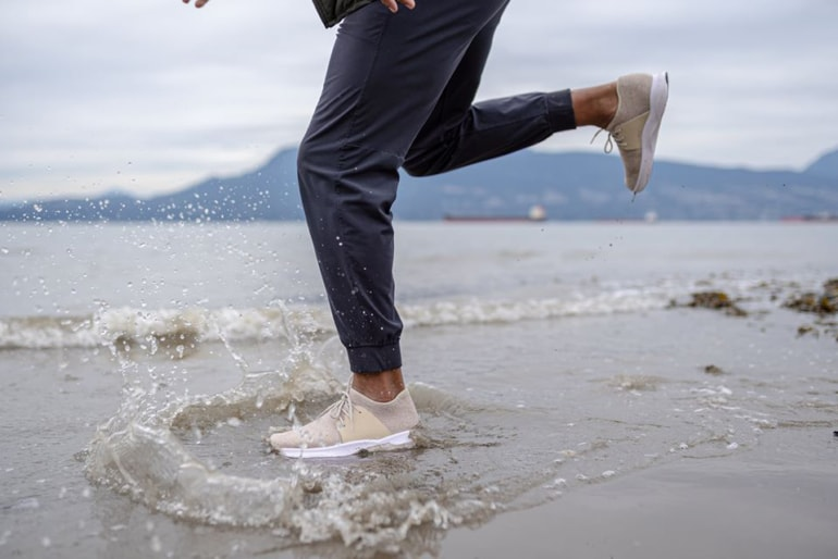 A person dancing through the water in their Vessi shoes
